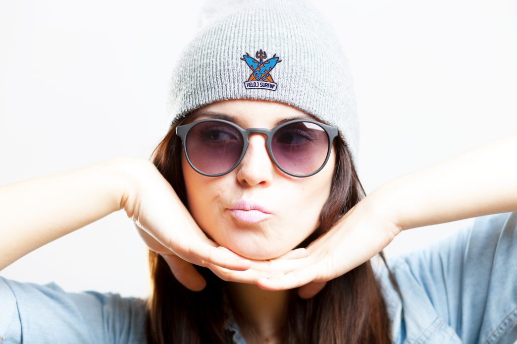 Young woman wearing sunglasses and HELL SURFIN' beanie hat